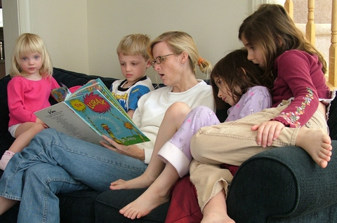 Mother reading book to children