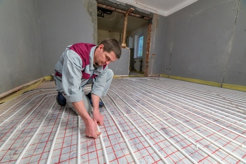 Worker installing in-floor heating system