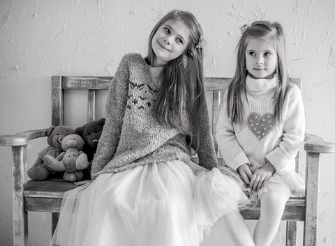A b/w photo of two girls sitting on a wooden bench