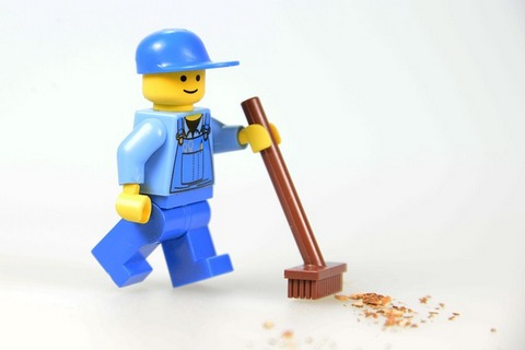 A Lego figurine holds a brush and cleans the floor