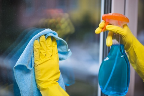 Cleaning a window with window cleaner and cloth, while wearing gloves