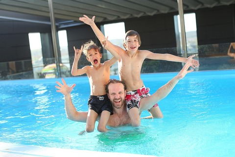 Father having fun with his sons in the swimming pool