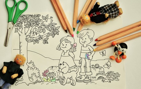A drawing of a tree with birds, girl, boy and puppy, with coloured pencils and toys.