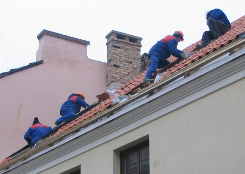 Workers putting roof tiles on