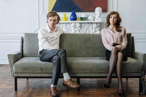 A man and a woman sitting on a couch apart