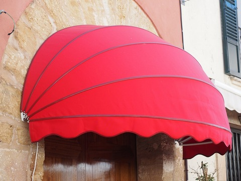 Dome shaped red awning above entrance door