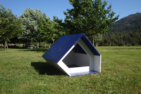 An unusually shaped dog house on a lawn
